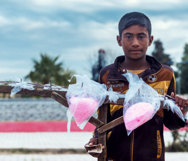 Kirkuk, Iraq - November 26, 2015: Syrian orphan in Iraq selling sweet inside park