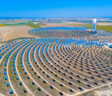 Seville, Spain - June 10, 2018: Solar tower surrounded by mirror panels harnessing the sun's rays to provide alternative renewable green energy. Situated in Andalucia, Spain.