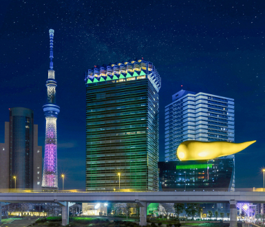 Tokyo, Japan - March 25, 2020: Night view of the illuminated Japan tallest tower Tokyo Skytree and the Olympic golden flame shape sculpture by Stark for the Asahi Beer Headquarter Building in Asakusa.