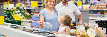 Cheerful young man and woman with little daughter holding shopping trolley with good in store