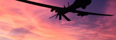 Silhouette de drone militaire sur fond coucher de soleil.