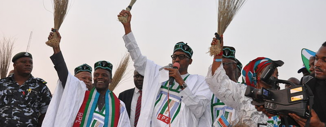 general_buhari_holding_a_broom_at_a_campign_rally.jpg