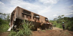 A MONUSCO Peacekeeper stands near the wreckage of a nepalese armored vehicle which was hit the previous year in an ambush from ADF militia in the Beni region, the 13th of March 2014.