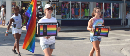 People marching in the Key West Gay Pride parade carry a memorial banner honoring those killed in the terror attack at the nightclub in Orlando, June 12, 2016. Credits: Chuk Wagner/Shutterstock