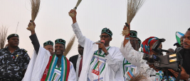 general_buhari_holding_a_broom_at_a_campign_rally.jpg