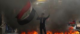 Un manifestant irakien bloque une rue pour protester contre le gouvernement irakien