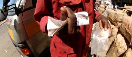 Hand holding several bills of Kenyan shilling