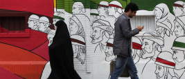 TEHRAN, IRAN - APRIL 3, 2012: People walking in Imam Khomeini Street with street art wall in background