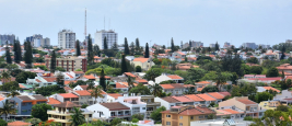 A colorful elevated view of houses in a residential area in Maputo, the capital of Mozambique with tall buildings in the background