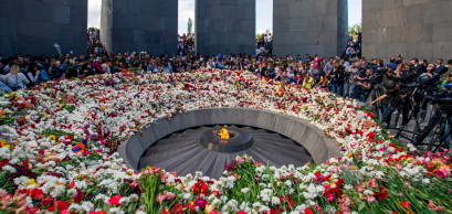 Yerevan, Armenia - April 24, 2018: Armenians laying flowers at the eternal flame in the center of the twelve slabs of Armenian Genocide memorial