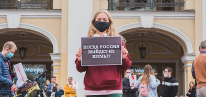 """Saint Petersburg, August 2020: a protester holds a poster """"When will Russia come out of coma?"""" at a rally."""