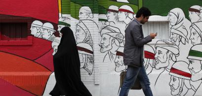 TEHRAN, IRAN - APRIL 3, 2012: People walking in Imam Khomeini Street with street art wall in background