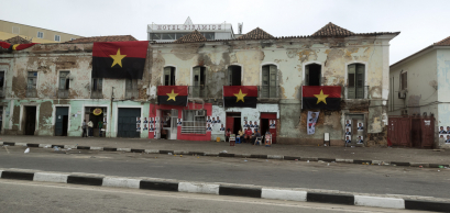 Residents sit outside on election day in Angola underneath the flags of the ruling People's Movement for the Liberation of Angola (MPLA) party, on 23 August 2017
